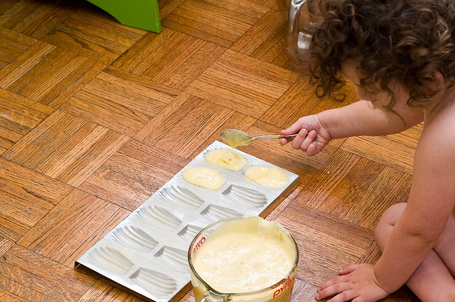 Child filling madeleine cookie molds with batter