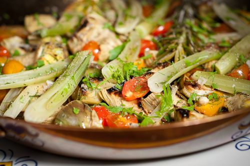 Saute pan full of braised artichokes, fennel and cherry tomatoes